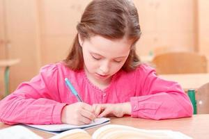 piccola ragazza che scrive durante le lezioni foto