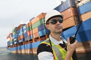 uomo che usando walkie-talkie al terminal container foto