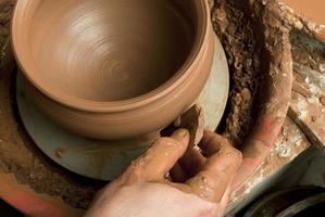 mani di un vasaio, creando un vaso di terracotta foto