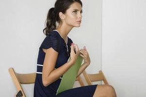 donna premurosa in abito blu con appunti foto