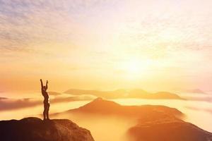 uomo con le mani in alto sulla cima di una montagna foto