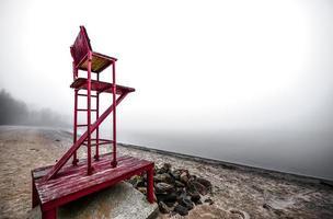 sedia vuota del bagnino su una spiaggia nebbiosa. foto