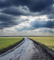 strada sporca all'orizzonte e cielo drammatico foto