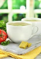 tazze di zuppa con cubetti di brodo sul tavolo di legno foto