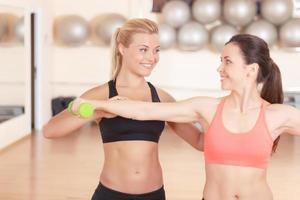 istruttore di fitness aiutando la donna in palestra foto