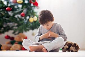 ragazzino carino e il suo giocattolo scimmia, giocando sul tablet foto