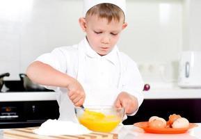 giovane ragazzo cottura uova da montare foto