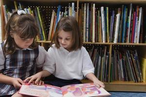 due bambini che leggono insieme sul pavimento in una biblioteca foto