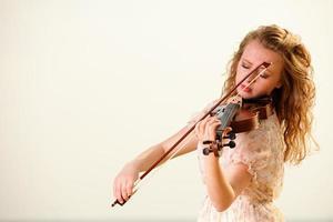 la ragazza bionda con un violino all'aperto foto