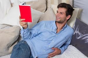 giovane uomo del brunette che legge un libro foto