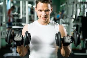 uomo con attrezzi per allenamento con i pesi foto