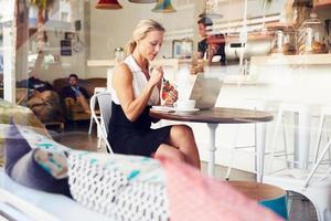 donna d'affari seduto a un tavolo nella piccola caffetteria foto