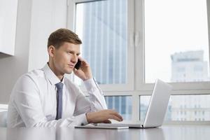 metà uomo d'affari adulto su chiamata mentre si utilizza il laptop a casa foto
