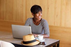 giovane donna di colore che sorride e che per mezzo del computer portatile