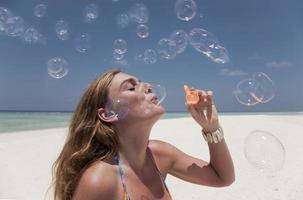 donna che soffia bolle sulla spiaggia