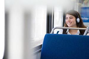 donna che ascolta la musica sul treno foto