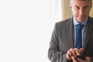 uomo divertente che manda un sms sul suo telefono cellulare foto