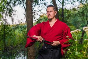 uomo in uniforme di abbigliamento giapponese etnico samurai con spada katana foto
