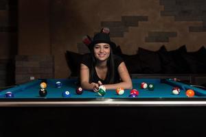 giovane donna sdraiata sul tavolo da biliardo