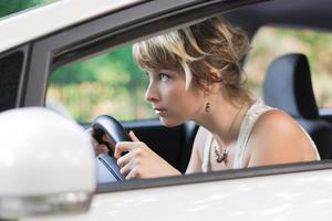 giovane donna che impara a guidare auto e sporgendosi in avanti foto