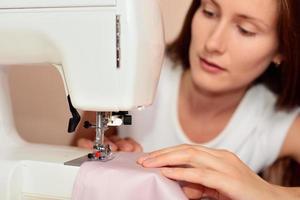 giovane donna attraente cucito foto