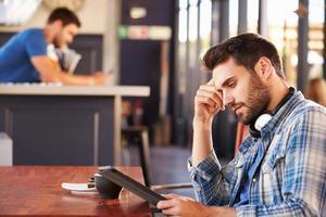 uomo che utilizza la tavoletta digitale in una caffetteria