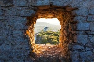 vecchio mulino a vento attraverso la finestra nel muro della fortezza foto