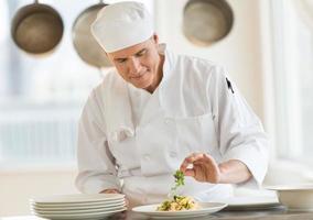 chef che guarnisce piatto in cucina commerciale