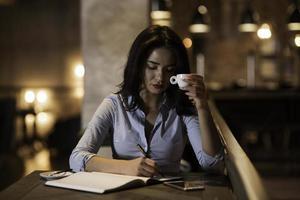 Ritratto di una donna d'affari elegante, concentrata, bere caffè e scrivere le note nel moderno ristorante foto