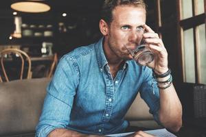 imprenditore che mangia e lavora al street cafe foto