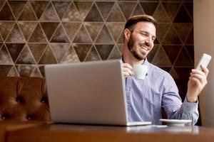giovane che lavora al computer portatile nel caffè foto