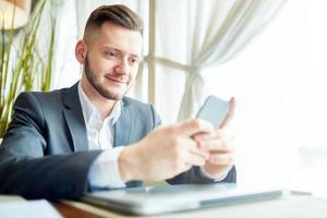 uomo d'affari tramite smartphone foto