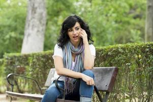 felice attraente donna latina che indossa abiti casual, seduto su una panchina del parco mandare SMS e parlare sul suo telefono cellulare intelligente in un lussureggiante parco verde o prati foto