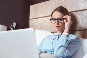 donna di affari che utilizza computer portatile nella camera di albergo foto