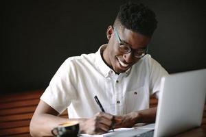 libero professionista seduto con un laptop facendo il suo lavoro in un bar foto
