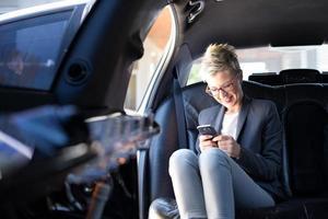 donna di affari che manda un sms e che sorride foto