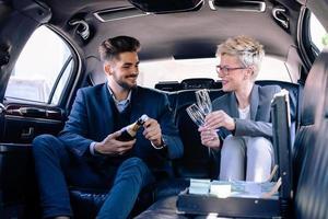 soci d'affari con champagne in limousine foto