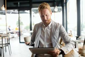 uomo d'affari occupato che gode del caffè mentre online foto