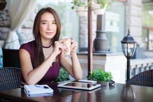 donna di affari felice che lavora all'aperto con il computer portatile foto