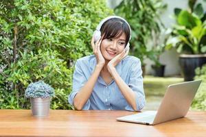 giovane donna asiatica che si rilassa ascoltando musica con il computer portatile che sente così felicità