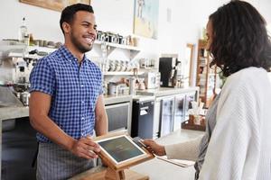 il barista maschio sorride ad un cliente femminile in una caffetteria foto