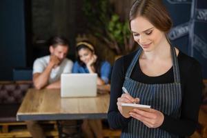 proprietario sorridente scrivendo sul blocco note mentre in piedi contro il cliente