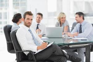 uomo d'affari con i colleghi che discutono in ufficio foto