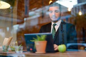 uomo d'affari che utilizza computer portatile nella caffetteria foto