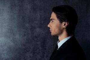 foto di vista laterale del giovane duro in abbigliamento formale