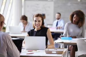 donna di affari che utilizza computer portatile nel dipartimento di servizio di assistenza al cliente foto