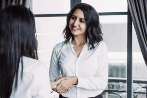 donna sorridente di affari che stringe le mani con il partner alla finestra del caffè foto