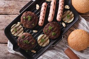 hamburger e salsiccie sul primo piano orizzontale di vista superiore della leccarda foto