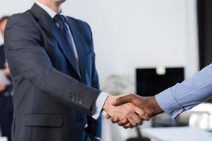 gara di due mix irriconoscibile uomo d'affari stringere la mano accordo centro di coworking colleghe team di business foto
