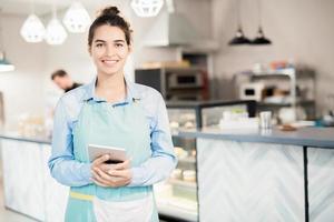 cameriera di bar sorridente che posa nel caffè foto